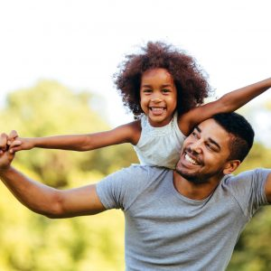 Portrait of young father carrying his daughter on his back in nature